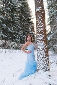 Beauty girl in blue dress in winter forest — Stock Photo
