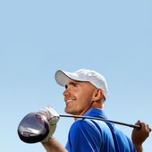 Smiling golfer holding golf club over shoulder — Stock Photo