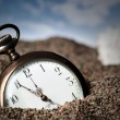 Old pocket watch buried in sand — Stock Photo