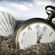 Stock Photo: Old pocket watch buried in sand