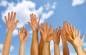 Hands raised up in air across blue sky — Stock Photo