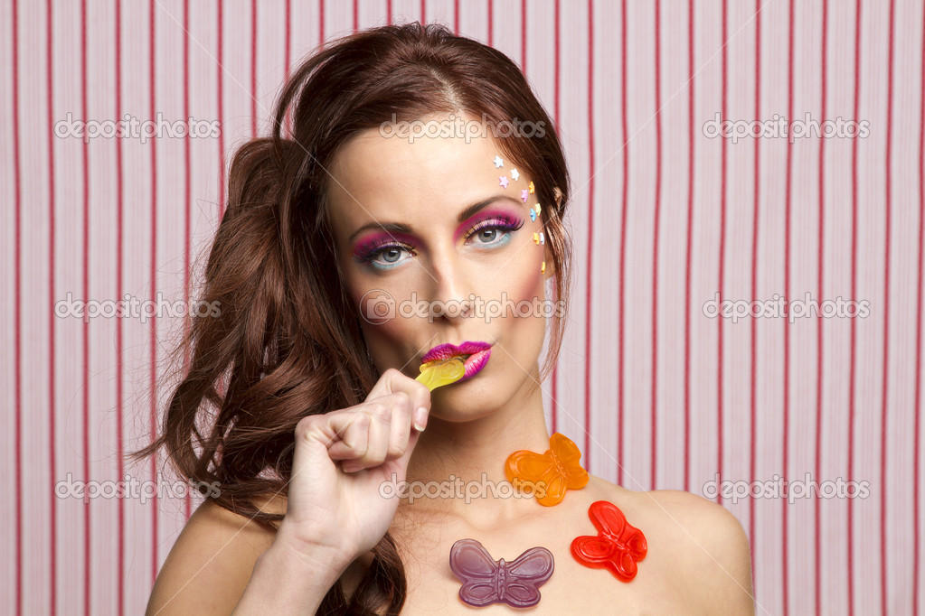 Young woman with colorful makeup and star candy glued to her face and gummy butterfly glued to her body, sucking on the wing of a yellow butterfly — Stock Photo #10381241