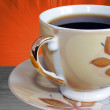 Close-up on cup of coffee over orange background — Stok fotoğraf