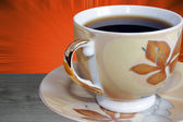 Close-up on cup of coffee over orange background — Stock Photo