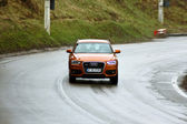Orange car in the road to Poiana Brasov — Stock Photo