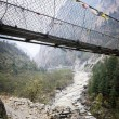 Hanging footbridge ower river, Nepal — Stock Photo