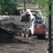 Stock Photo: Mini wheel excavator working in city park at spring