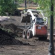 Mini wheel excavator working in city park at the spring - Stock Photo