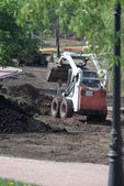 Mini wheel excavator working in city park at the spring — Stock Photo