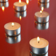 Many small decorative candles burning on a red background — Stock Photo