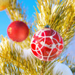 Christmass toys hang on a snow-covered tree against the blue sky - Stock Photo