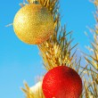 Christmass toys hang on a snow-covered tree against the blue sky — Stock Photo
