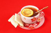 Cup of black tea with a lemon on a red cloth — Stock Photo