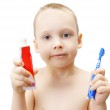 The little boy shows a tooth-brush and a tube with tooth-paste — Stock Photo