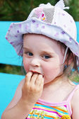 Little girl which eats a raspberry — Stock Photo