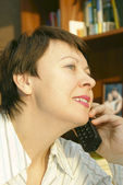 The woman attentively speaks on the phone — Stock Photo
