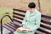 The young woman reads the book in autumn park — Stock Photo