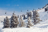 Chair ski lifts with skiers over blue sky in the mountains — Stock Photo