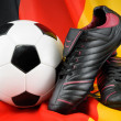 Soccer ball and shoes on German flag — Stock Photo