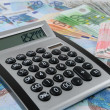 Calculator on Euro banknotes - Stock Photo