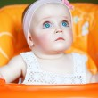 Cute baby with blue eyes in orange chair — Stock Photo