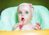 Little funny child with pink spoon in mouth — Stock Photo