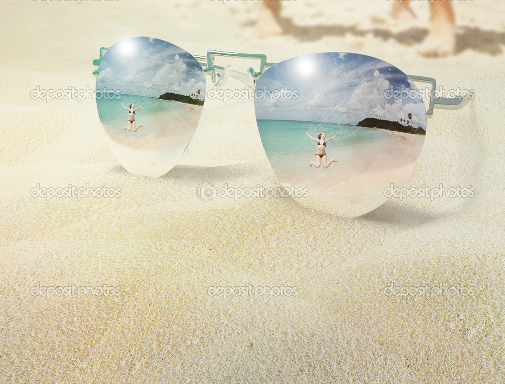 The vacation reflection in the mirror glasses which lays on the beach sand the woman is jumping on the beach  Stock Photo #9036836