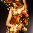 Sensual woman in long yellow dress and flowers — Stock Photo