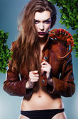 Pretty erotic devil woman in leather jacket with chameleon under — Stock Photo