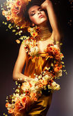 Sensual woman in long yellow dress and flowers — Foto Stock