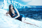 Woman in dress on the snowy beach and iceberg — Stock Photo