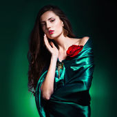 Art portrait of a beautiful woman in green dress whith rose — Stock Photo