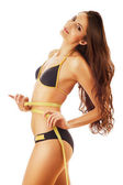 Smiling slimming woman with long hair in swimsuit with measure — Stock Photo