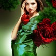 Attractive woman in green fabric with red roses — Stock Photo