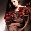 Beautiful woman in chocolate fabric with chocolate roses — Stock Photo