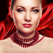 Beautiful woman with accessorize on red fabric background — Stock Photo