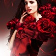 Sexy woman in red fabric with red roses — ストック写真