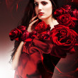 Sexy woman in red fabric with red roses — Stok fotoğraf