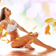 Sporty sexy woman siting on the floor with yellow leaves — Stock Photo #9269201