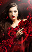 Attractive woman in red drapery with red roses — Stock Photo