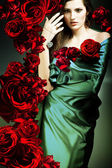 Beautiful woman in green fabric with red roses — Stock Photo