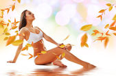Sporty sexy woman siting on the floor with yellow leaves — Stock Photo