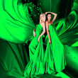 Stock Photo: Two women in green dress with long hair and hearts on red draper