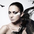 Close up portrait of woman with black splash and crow - Stock Photo