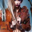 Pretty erotic devil woman in leather jacket with two violins — Stock Photo