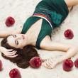 Woman with red apples on the sand in green dress — Stock Photo
