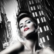 Attractive brunette woman with red lips in rainy city - Stock Photo