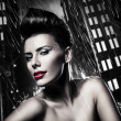 Sexy brunette woman with red lips in rainy city - Stock Photo