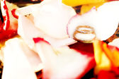 Golden rings and rose petals — Stok fotoğraf