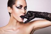 Närbild porträtt av brunett kvinna med svart handske i mun — Stockfoto